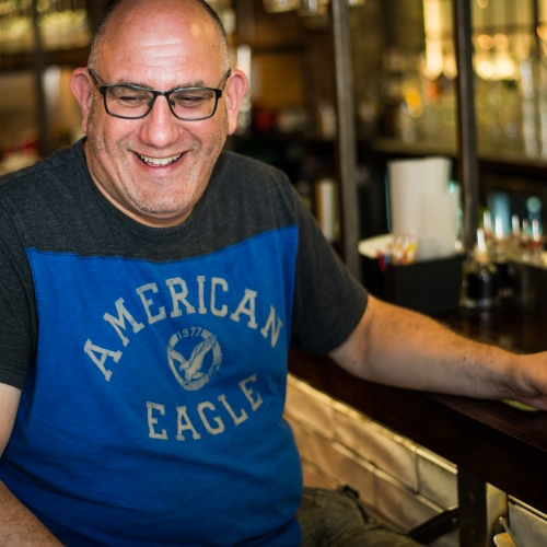 Gary mazin sitting at a bar, wearing a blue top and laughing