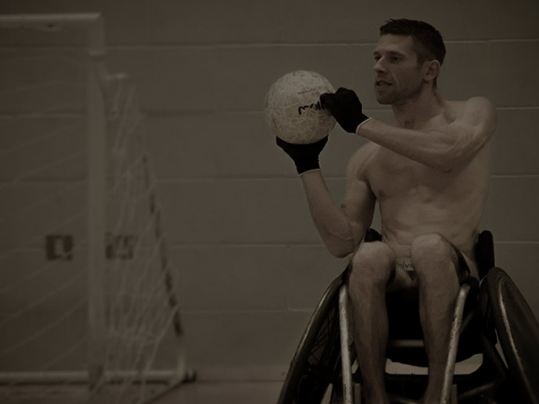 Naked man in wheelchair playing basketball