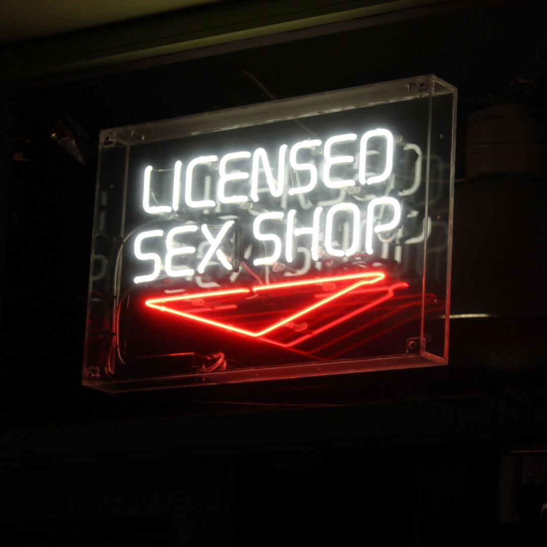 A neon sign reading 'Licenced sex shop' is lit in white against a black background, there is a red neon sign pointing downwards