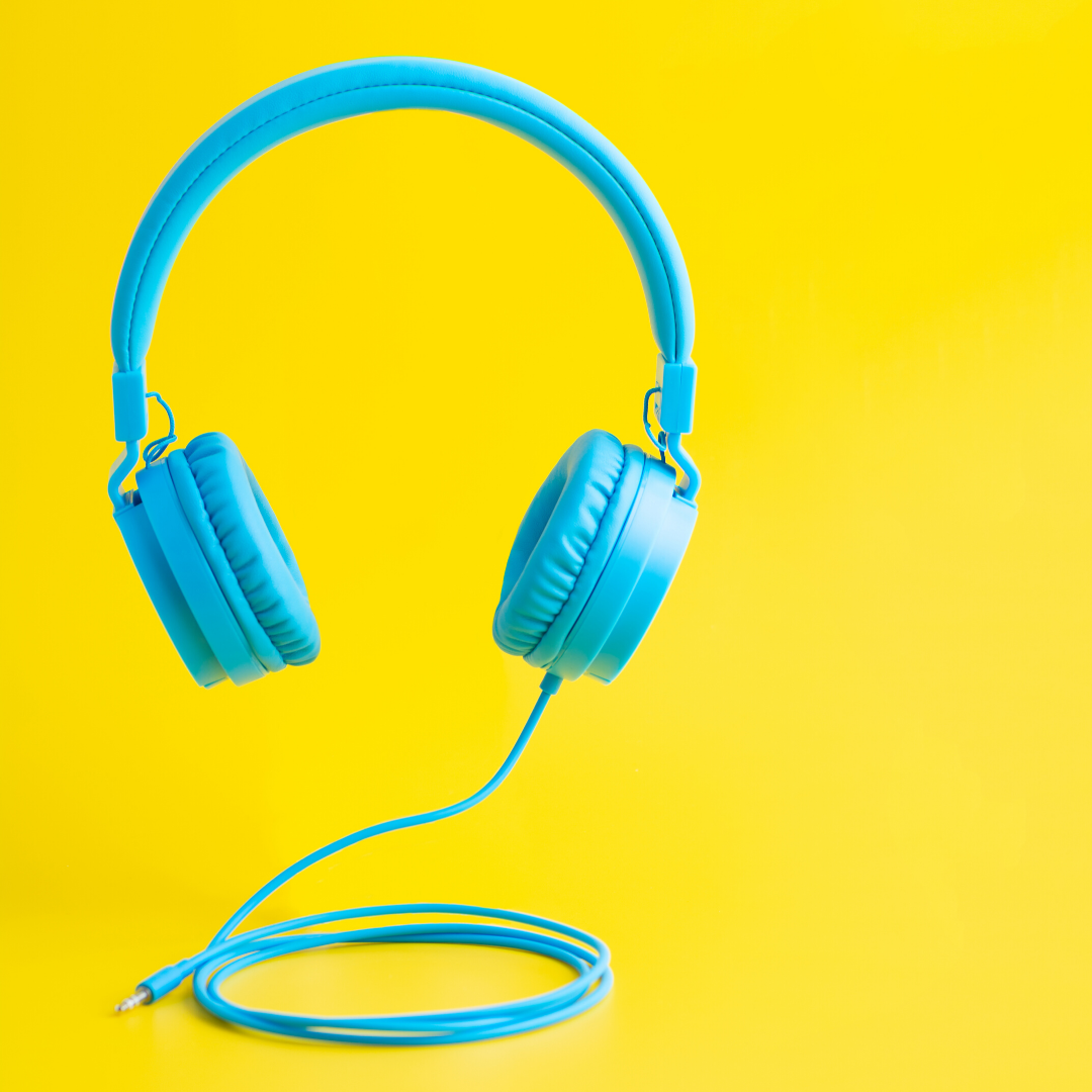A pair of pale blue headphones are against a bright yellow background