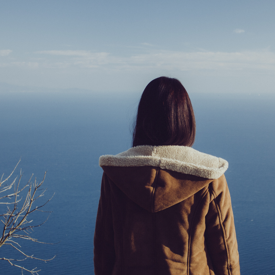 A girl is standing with her back to the camera looking out across a blue sea, she has dark hair tucked into a beige sheepskin jacket