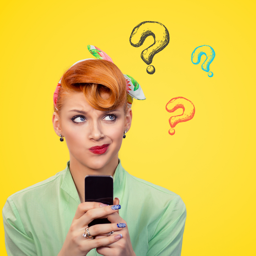 A girl stands in front of a yellow background. She has orange hair styled in a retro fashion with a headscarf and a pale green shirt. She is holding her phone in front of her and is looking off to her left with a thoughtful expression on her face. there are cartoon question marks to the side.