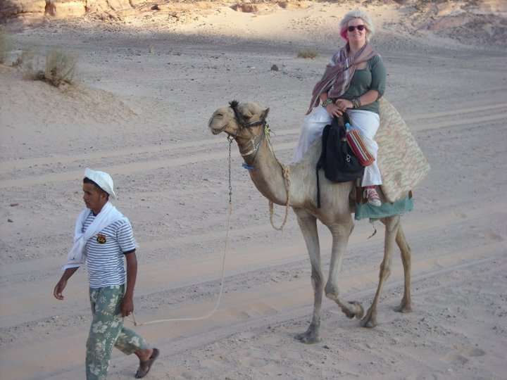 Emily on a camel being led.