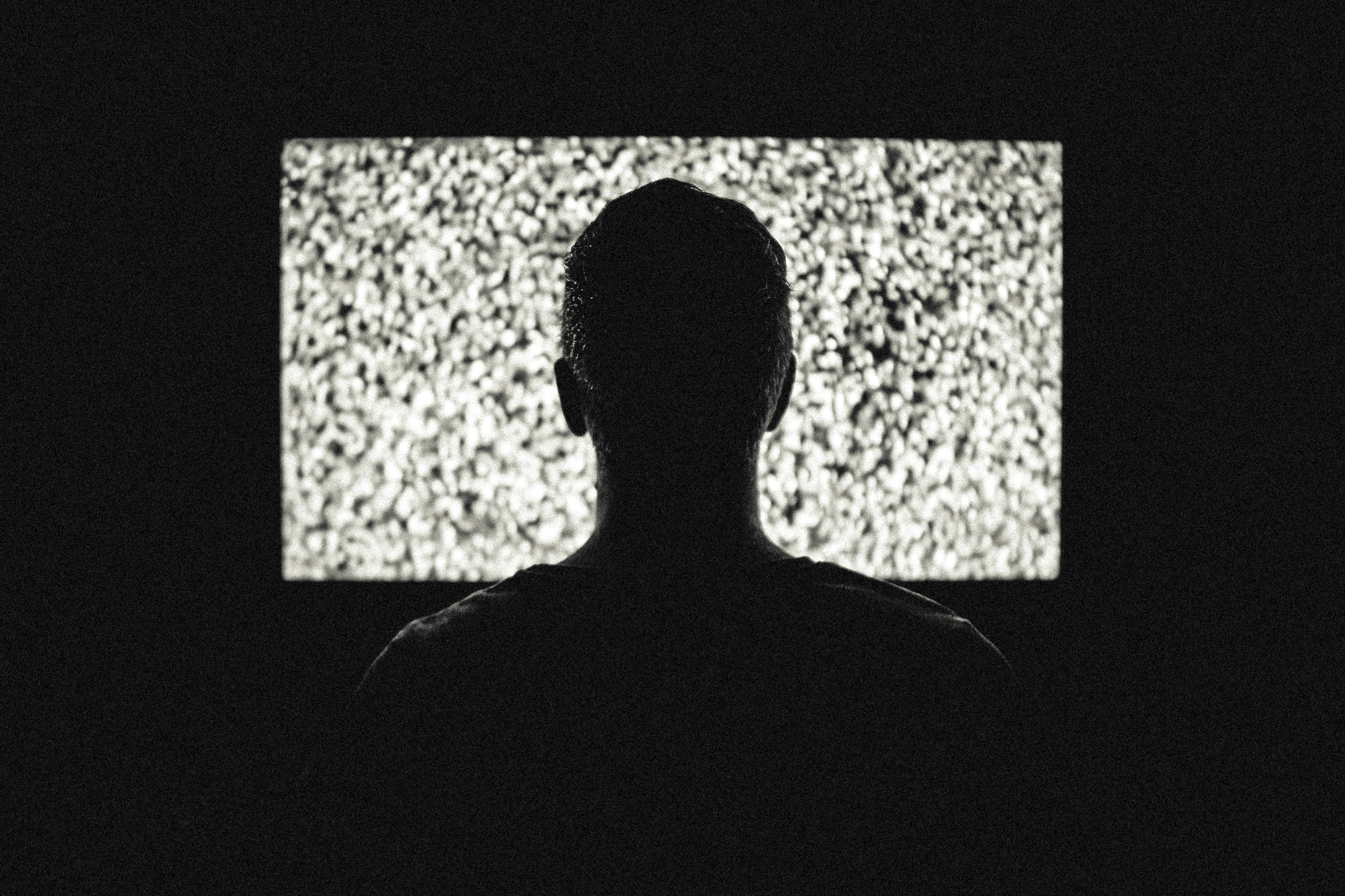 A man starring at a TV in a dark room