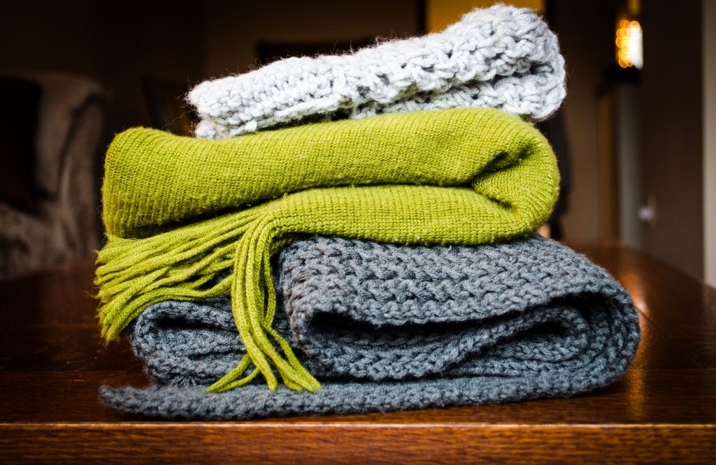 light grey, lime green and dark grey knitwear folded on top of one another