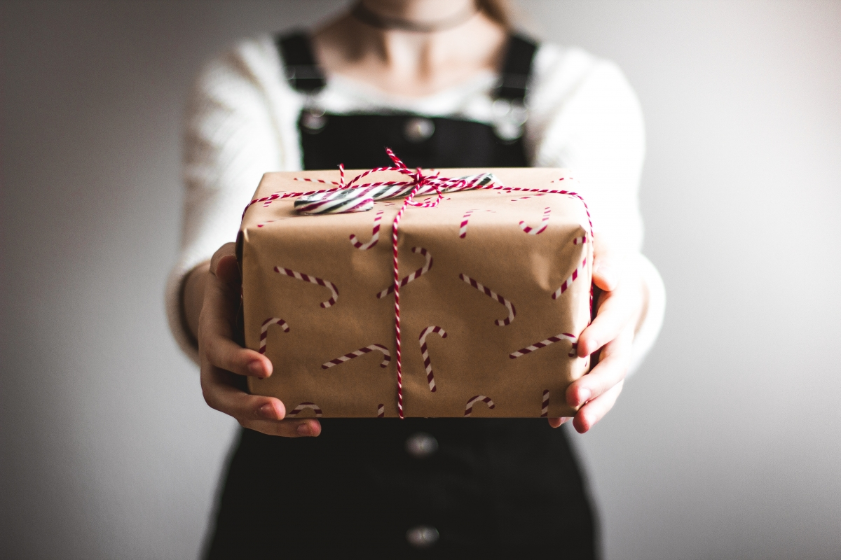 a girl holding a christmas present wrapped in brown paper