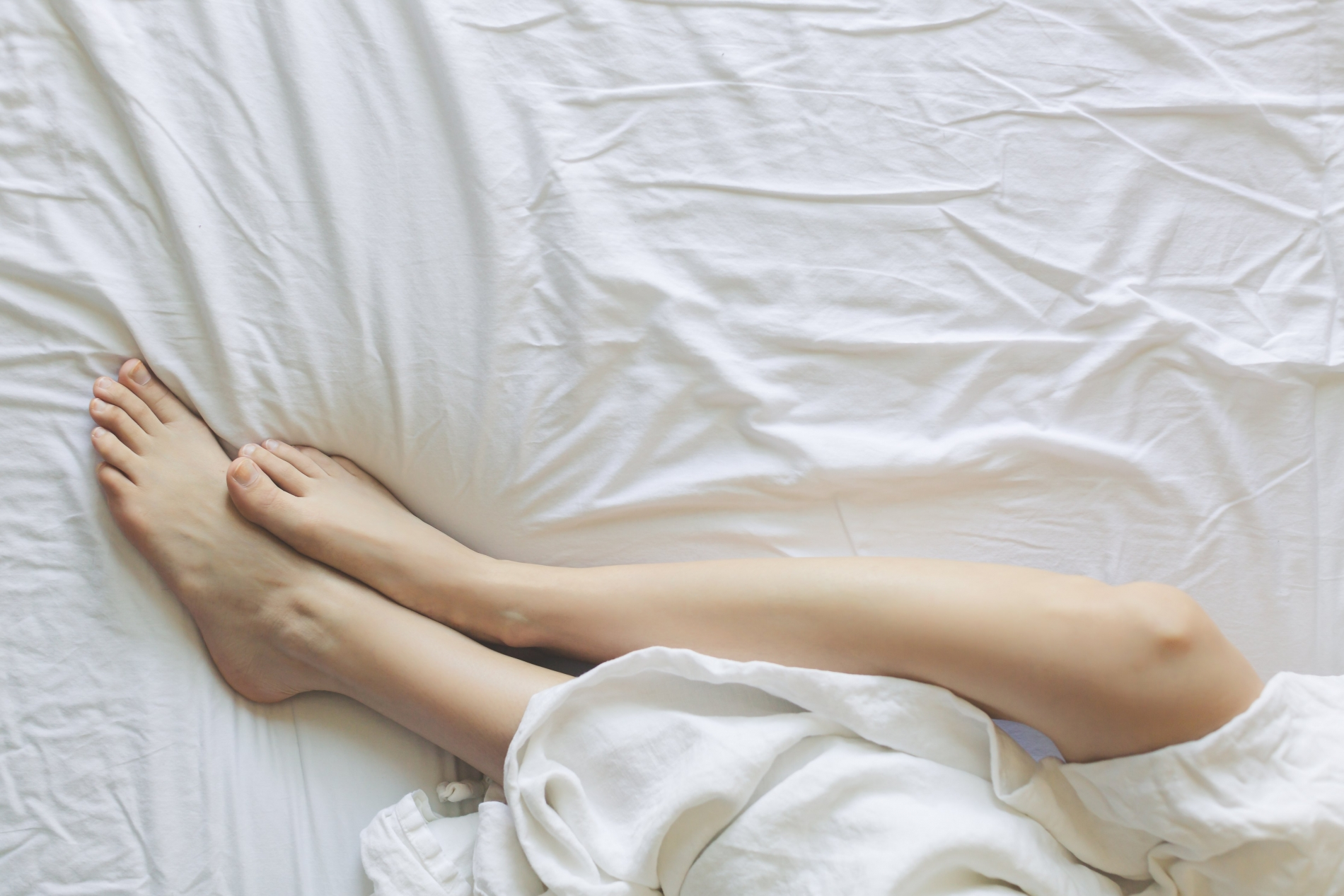 a man and woman's legs partly covered with a bed sheet
