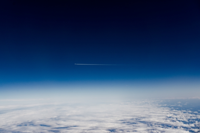 The earth and clouds below, a plane cruising at high altitude and above, space