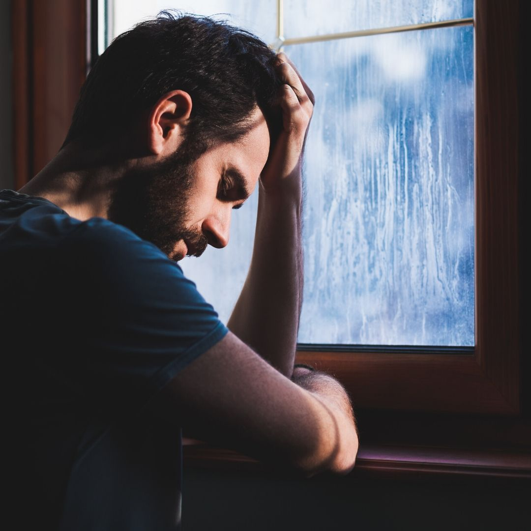A man with dark hair and a beard looks down with a sad expression whilst leaning against a window with rain on the pane
