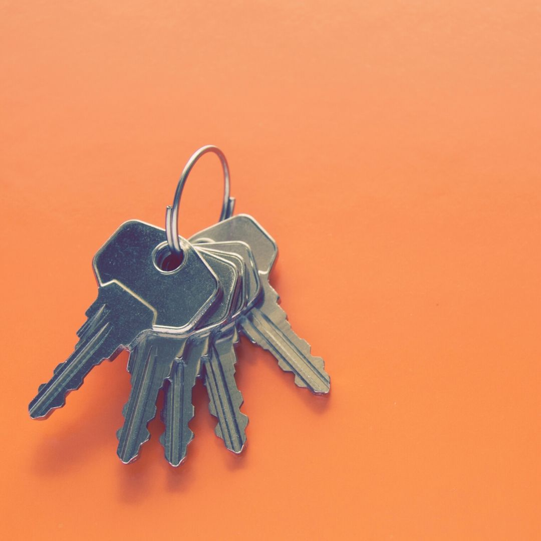 An orange background with a set of keys on a ring