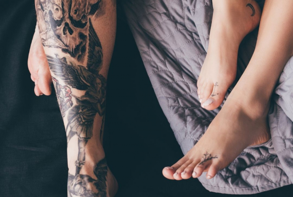 The tattoed legs and feet of a couple lying on a bed