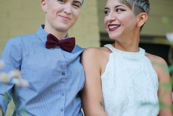 A female couple, both with very short hair. One wearing a white top, the other a blue shirt and dark red bow tie.