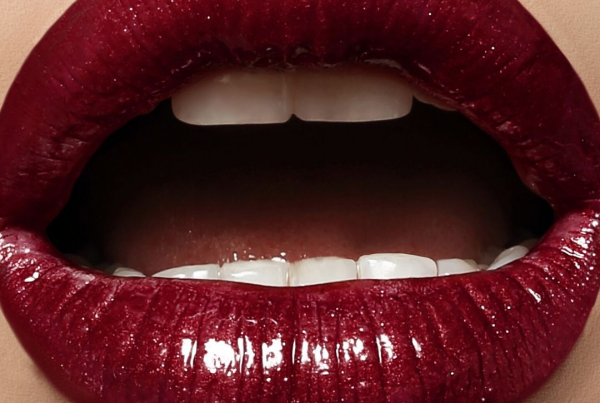 Deep red glossy lipstick painted on to an open mouth