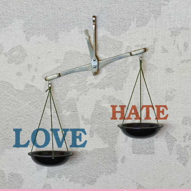 A set of scales hanging on a peg against a wall, one says Love the other says Hate
