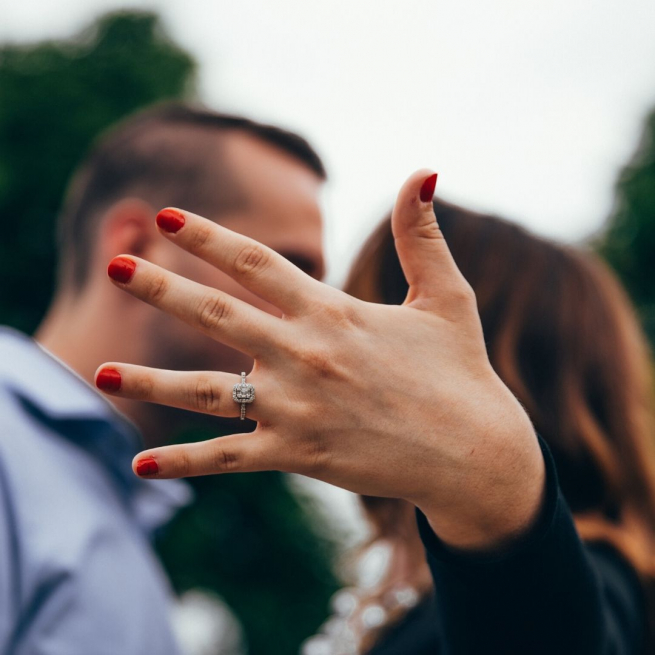 A woman holds her hand towards the camera showing her engagement ring. Blurred in the background she is kissing her fiance.