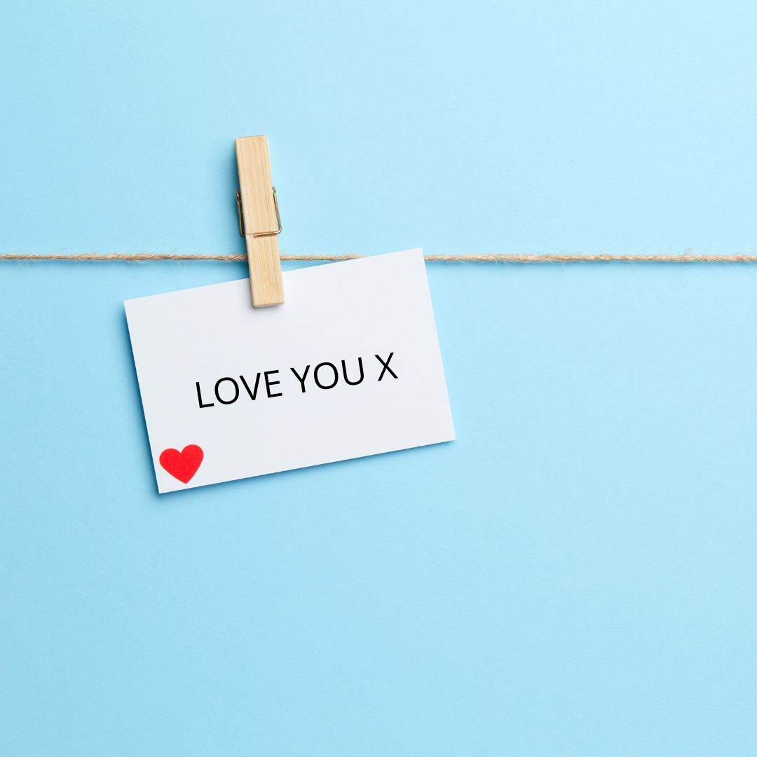 A white card with a peg holding it on a washing line. It reads 'Love You' with a red heart in the corner. The background is light blue