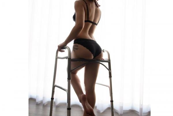 Josie poses in black bra and pants, leaning against her walking frame.