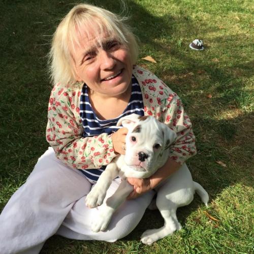 Becky Batten sat on grass cuddling a small white dog.