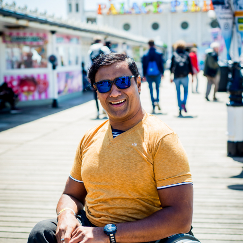 Jig sat in his wheelchair smiling on Brighton Pier
