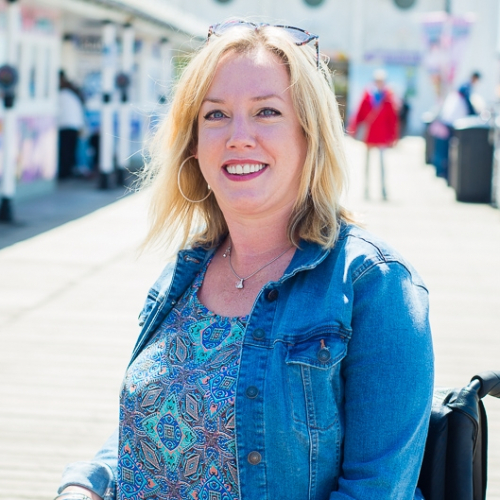 Zoe sat in her wheelchair smiling on Brighton pier