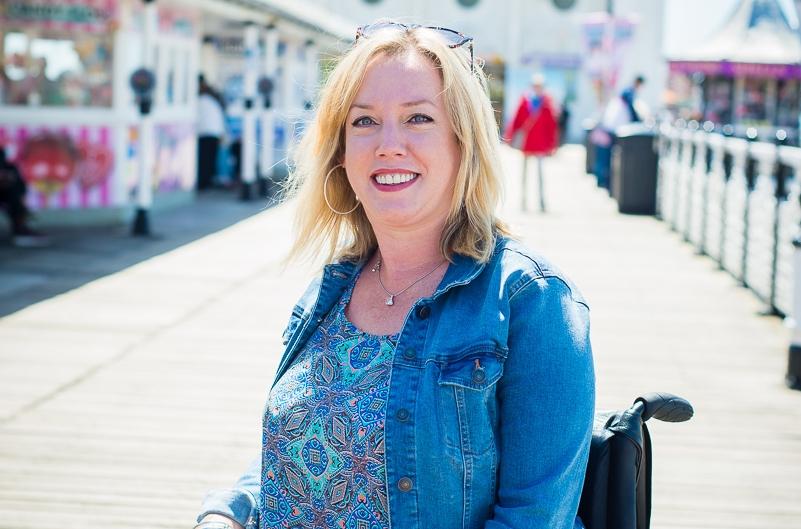 Zoe Lloyd sat in her wheelchair smiling on a pier