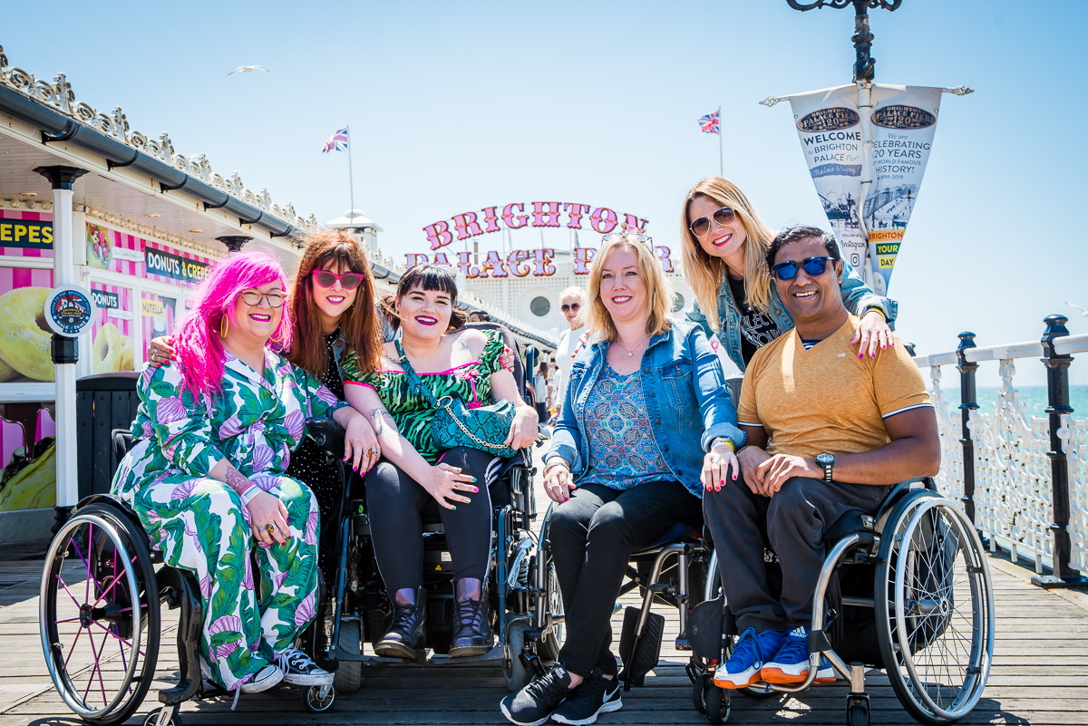 6 members of the Enhance the UK team on Brighton Pier. Emily, Kelly and Jig are sat in their wheelchairs and Jennie and Claire are stood behind them.