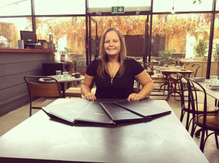 Carley Owen sits at a table in a restaurant wearing a black top and a huge beaming smile