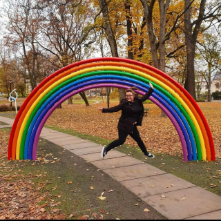 Carley is dressed in black and jumps in the air in front of a rainbow coloured archway which is situated in a park