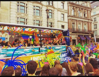 A brightly coloured float and a crowd of people attending pride and having a brilliant time