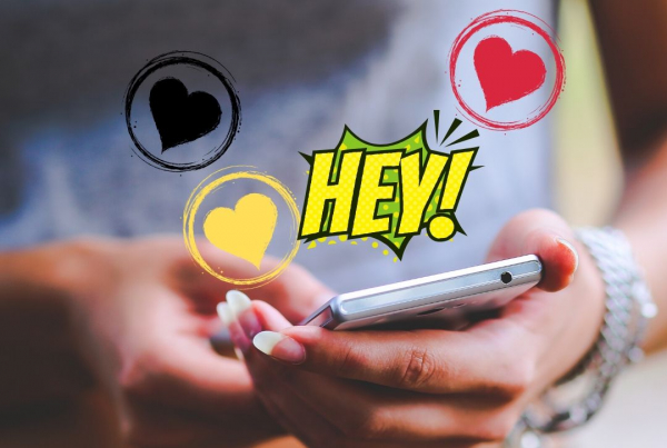 Online Dating when disabled - a womans hands hold a mobile phone whilst cartoon hearts and words fly out from the screen