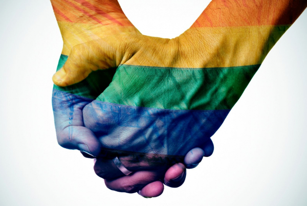 Two hands clasped together with the hands and arms painted in the pride flag