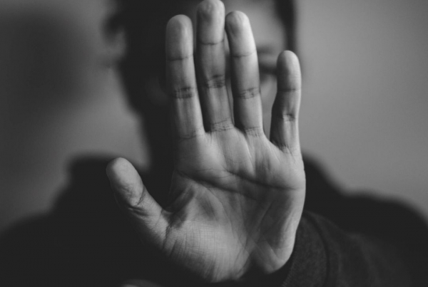 Rejection dating and disclosing disability - a black and white image with a hand hiding a persons face indicating STOP!