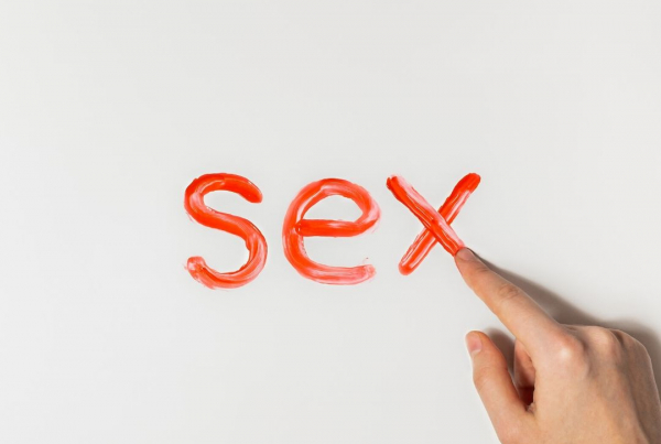 Doggy with CP - the word SEX written in orange paint on a white background with a hand