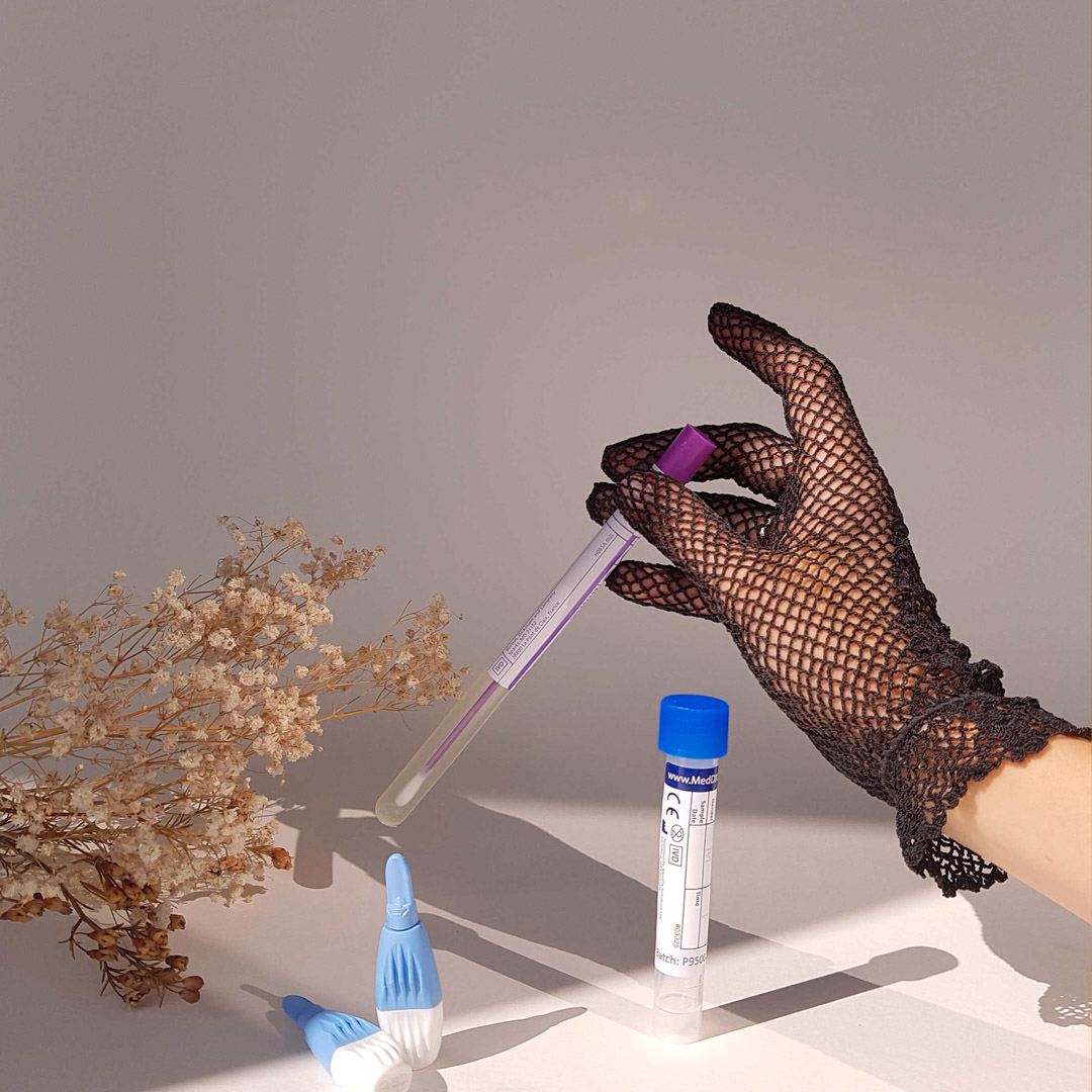 STI tests and a hand in a black lace glove holding one.
