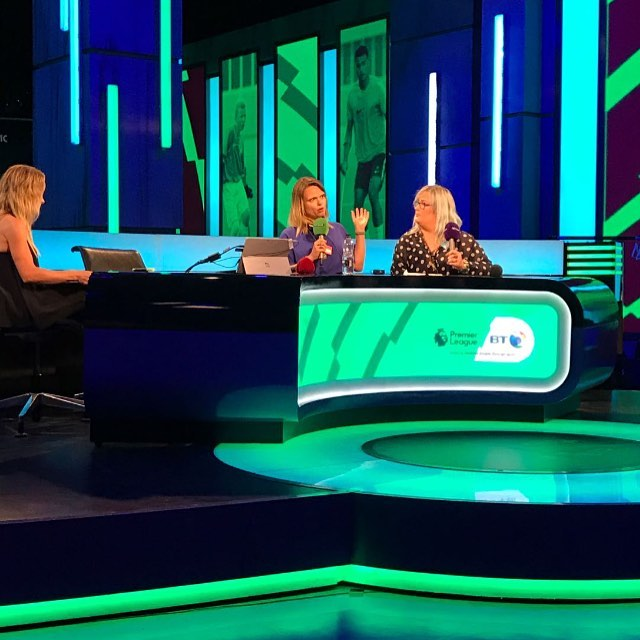 Jennie and Emily sat at the Premier League BT sport football desk being interviewed holding microphones.