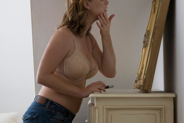 Boring, routine sex - a woman in her 40s wearing a bra and jeans looks in a mirror, which is placed on top of a chest of drawers, applying make-up