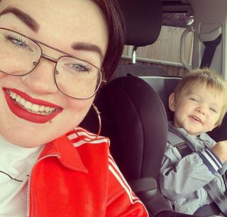 A selfie of Kelly and her two year old son Mason who is sitting in his car seat. Kelly has bright red lipstick on to matchher bright red adidas jacket.