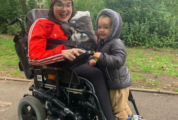 Kelly is pictured in her electric wheelchair with her son Mason and newborn Hunter. She is wearing a bright red adidas top, and is beaming at the camera