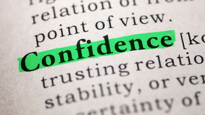 The word Confidence in a dictionary highlighted in green marker pen