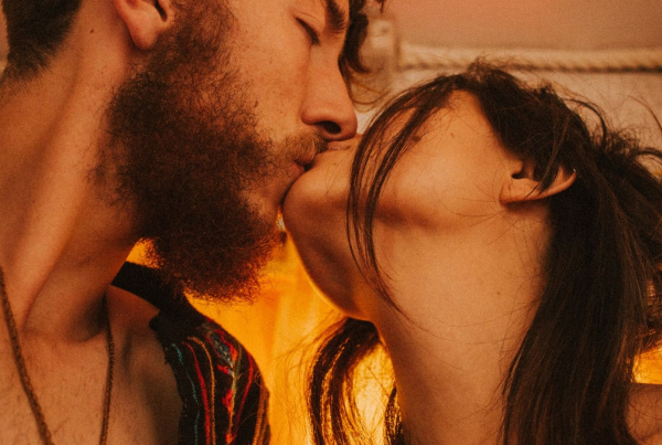 Turning Pain into Pleasure -A long haired bearded man in an open shirt bares his hairy chest whilst kissing a fair skinned dark haired woman