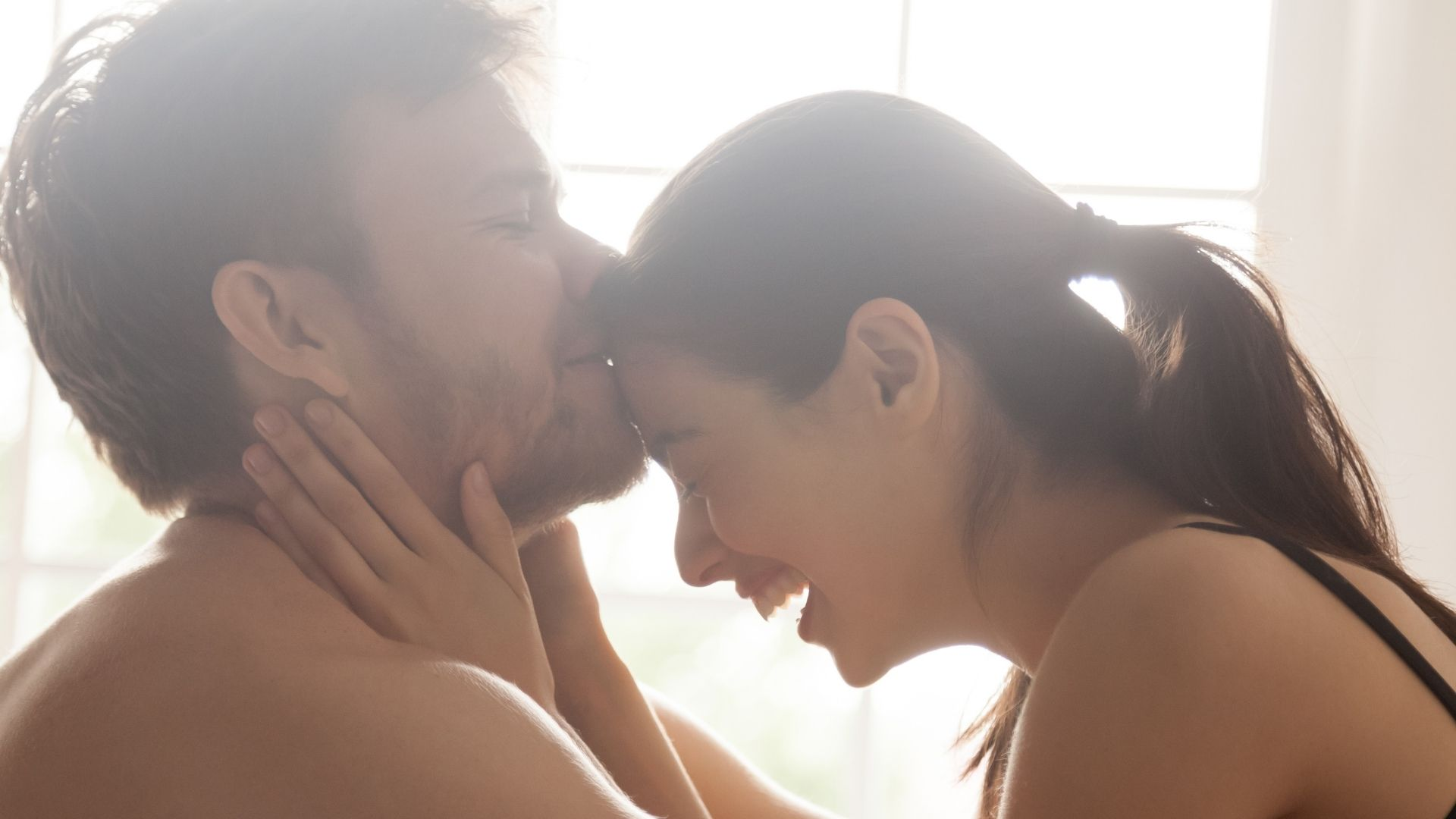 Grip Issues - How To Spice Up Your Sex Life - A dark haired woman leans forward to touch her male partner, he kisses her forehead. She is laughing and there is a window in the background