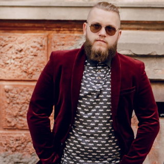 Styling It Out and Sweaty Pits - a trendy young guy wears a burgundy velvet suit jacket with a patterned T-shirt underneath. He has a hipster beard, a man bun and sunglasses