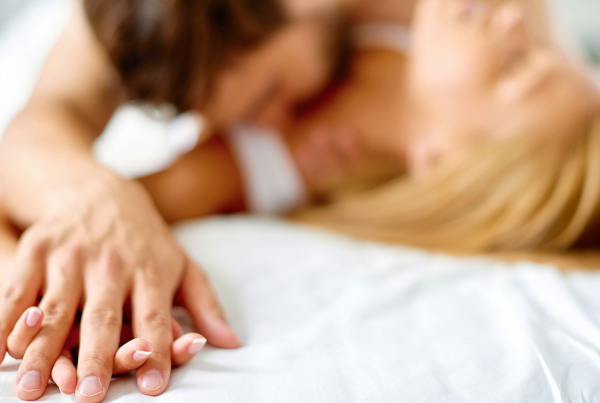 Sex when you have a live-in PA A man kisses a womans neck as she lies on a bed, their hands are entwined