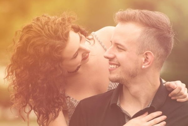 A woman with a disabled partner - she has brown curly hair leans down and puts her arms around a blonde man in a black top, they look lovingly at each other and smile