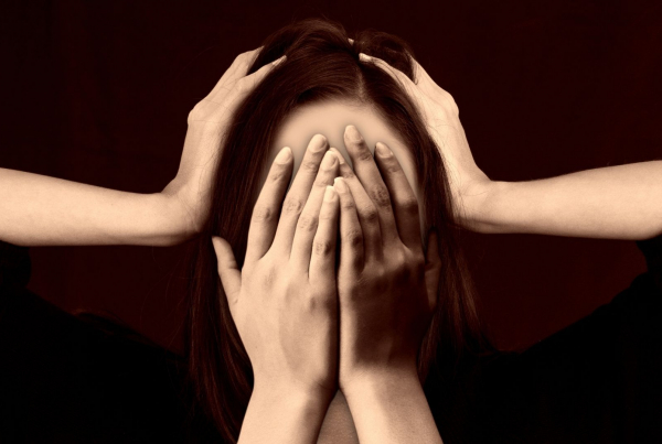 Stress Impacts Your Libido - a face covered with hands and another two hands pressing down on the side of the head