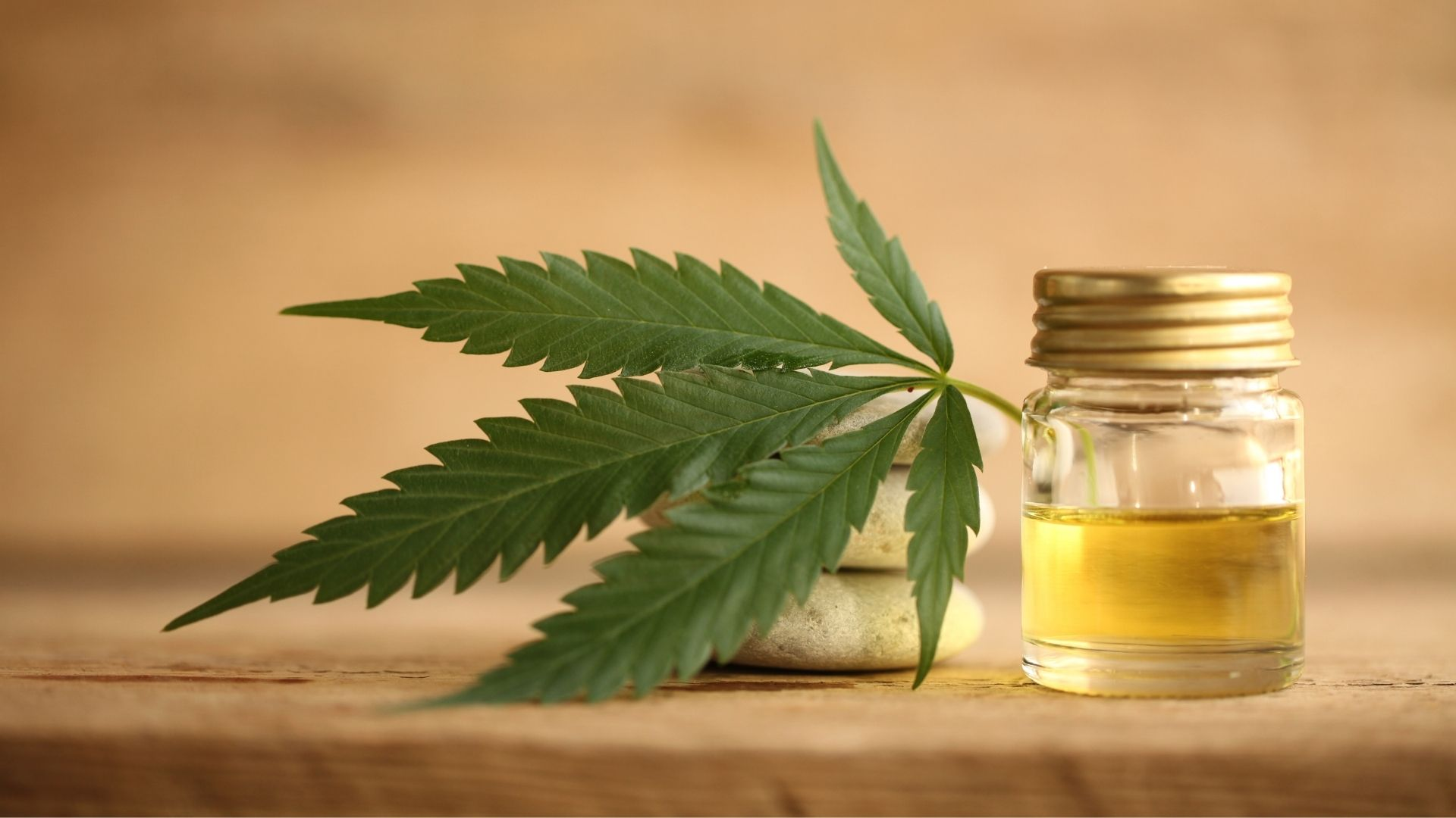 A jar of CBD oil with a plant leaf sitting on a wooden worktop