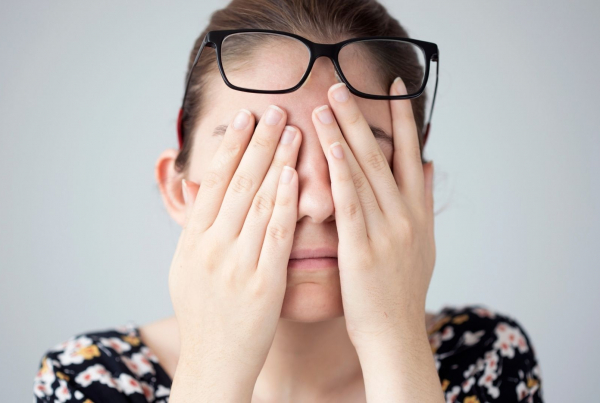 A brown haired woman presses her hands over her eyes exhausted with her glasses resting on her head. Her shoulders are visible and she wears a multicoloured top